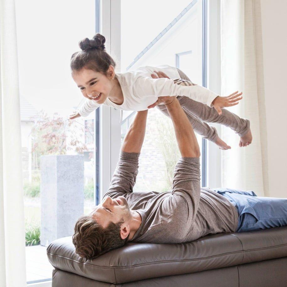 Un pere se joue avec sa fille dans un maison comfortable